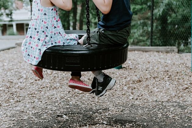 タイヤで作られたブランコに乗る男の子と女の子
