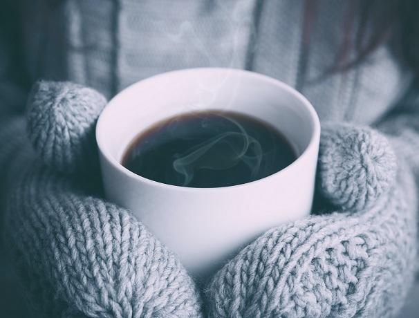 白いカップに入ったコーヒーを持つ、手袋をはめた手